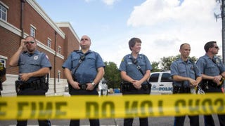 Police stand guard during a rally for Michael Brown outside the Ferguson Police Department in Missouri Aug. 30, 2014. Brown, an 18-year-old unarmed teenager, was shot and killed by Ferguson Police Officer Darren Wilson on Aug. 9.Aaron P. Bernstein/Getty Images