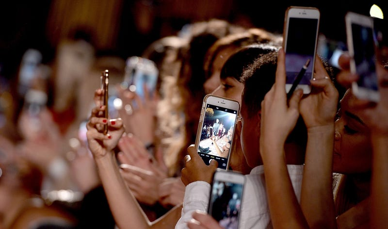 Everyone holds up their phones to take photos at London Fashion Week February 2017 (Photo by Jeff Spicer/Getty Images)