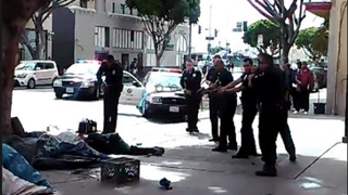 Several Los Angeles police officers stand with guns drawn over a homeless man who was reportedly shot some five to seven times March 1, 2015, during an altercation with police.Youtube