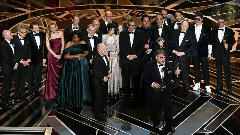 Guillermo del Toro and cast accepting an Oscar.