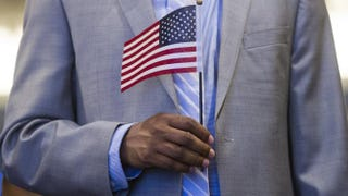 A man holds a U.S. flag prior to taking the citizenship oath to become a U.S. citizen during a naturalization ceremony at the U.S. Patent and Trademark Office in Alexandria, Va., May 28, 2015.  SAUL LOEB/AFP/Getty Images