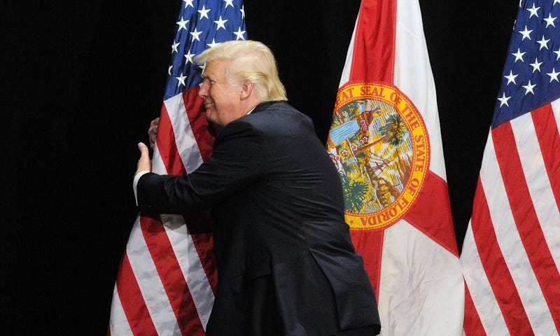 Republican presidential candidate Donald Trump embraces the United States flag during a campaign rally at the Tampa Convention Center on June 11, 2016 in Tampa, Florida