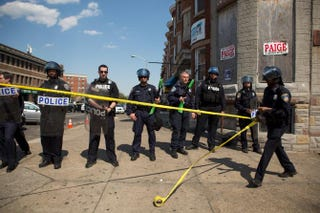 An officer rolls out police tape as other officers form a line to block North Avenue in Baltimore May 4, 2015, near the site of recent riots, and only several blocks away from where Freddie Gray was arrested April 12.Allison Shelley/Getty Images