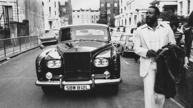 American soul singer Marvin Gaye (1939 - 1984) walking ahead of his Rolls Royce in Notting Hill, London.
