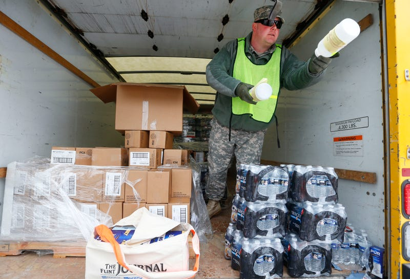 Michigan National Guard Staff Sgt. James Green hands out a water test kit to be distributed to residents Jan. 21, 2016, in Flint, Mich.