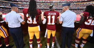 Washington Redskins players assist military personnel in holding the American flag. Twitter