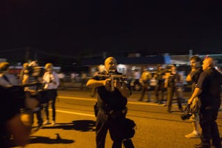 St. Ann, Mo., police Lt. Ray Albers points an assault rifle at a protester Aug. 19, 2014, in Ferguson, Mo. Albers, who was forced to lower his weapon and was escorted from the area by a police sergeant, according to a statement released by the St. Louis County Police Department, was relieved of duty and suspended indefinitely Aug. 20.Aaron P. Bernstein/Getty Images