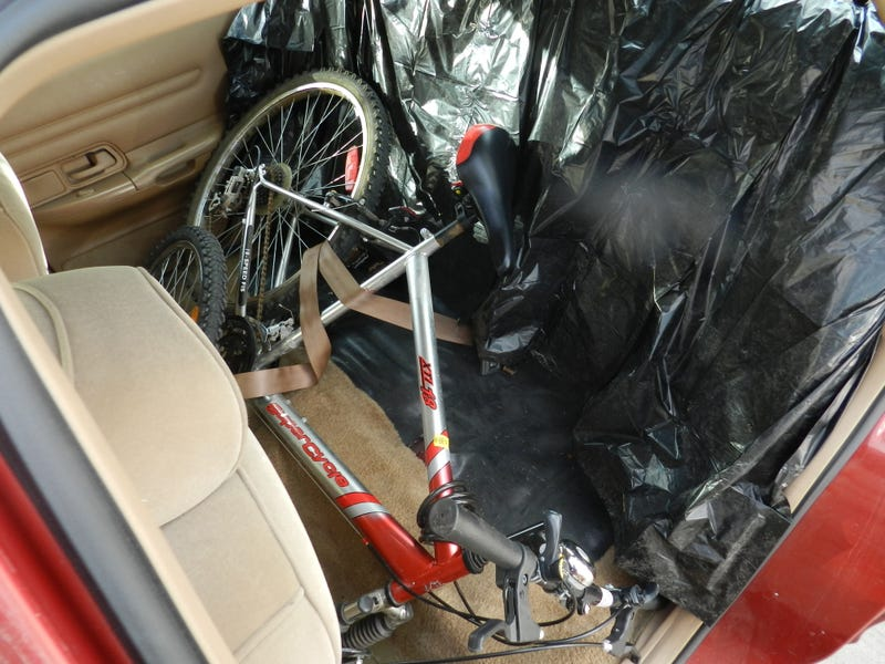 Illustration for article titled How To Fit A Bicycle (Or Two) Inside A Crown Vic in 3 Easy Steps!