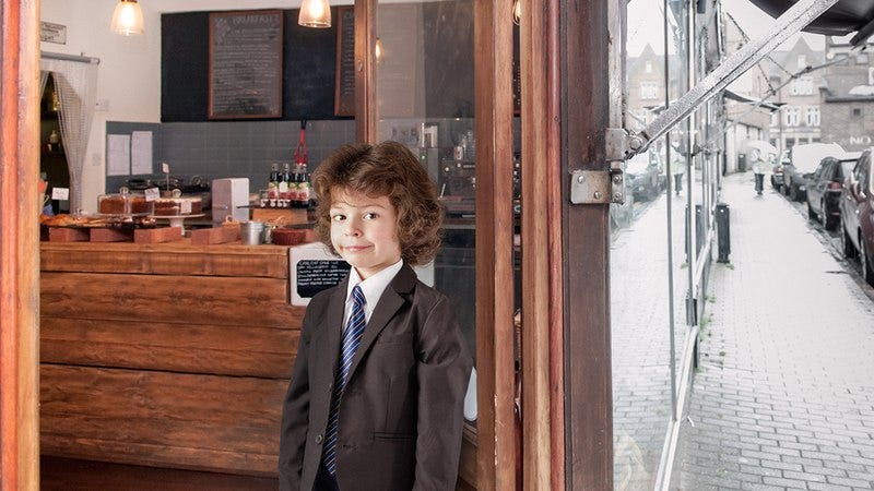 A little boy holding the door at a coffee shop.