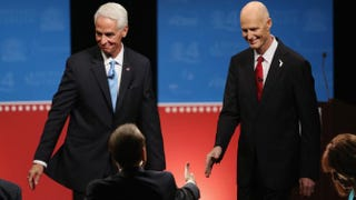 Charlie Crist, the former Florida governor and Democratic candidate to retake the seat, and Republican Florida Gov. Rick Scott shake hands with the moderators after finishing their televised debate at Broward College on Oct. 15, 2014, in Davie, Fla.Joe Raedle/Getty Images