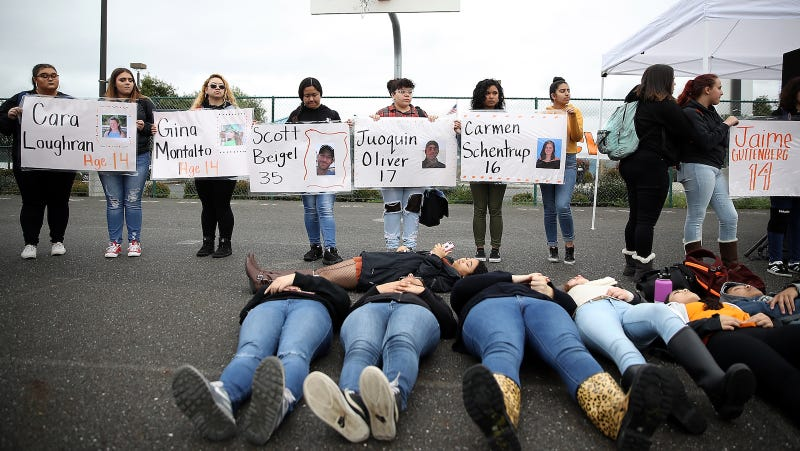James Logan High School students hold signs honoring students killed at Marjory Stoneman Douglas High School as they stage a die in and observe a moment of silence during a walk out demonstration on March 14, 2018 in Union City, California.