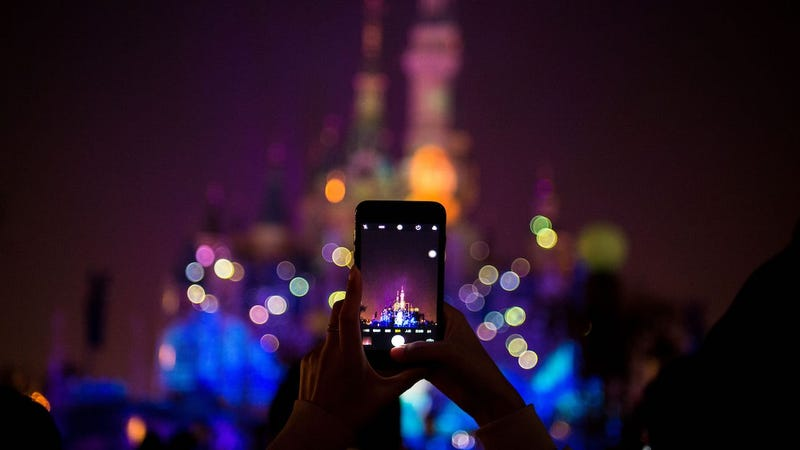 A tourist takes a photo with an iPhone at Shanghai Disneyland