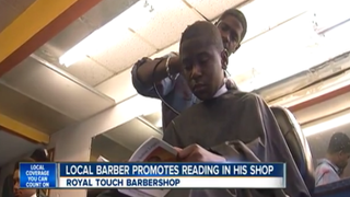 Royal Touch Barbershop owner Reggie Ross gives a touch-up to a young customer while he reads in Palm Beach County, Fla.WPTV screenshot