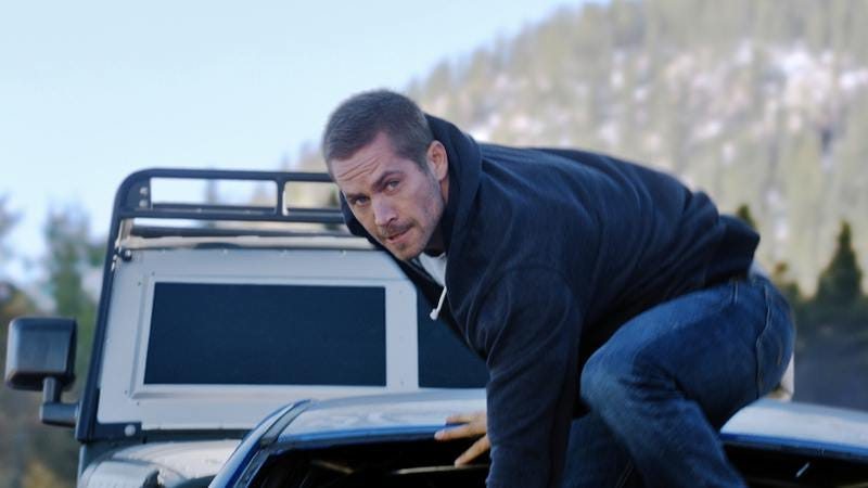 Illustration for article titled Furious 7 says goodbye to Paul Walker with wall-to-wall action absurdity