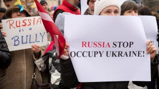 Protesters hold up placards during a demonstration against Russia's aggression in Ukraine at the Russian Embassy in Riga, Latvia, March 2, 2014.ILMARS ZNOTINS/AFP/Getty Images