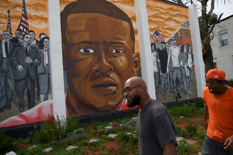 People walk past a mural of Freddie Gray on June 23, 2016, in Baltimore. Mark Makela/Getty Images