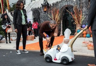 "President Barack Obama and first lady Michelle Obama gush over ""Lil' Pope,"" who arrived at the White House Halloween party in his own miniature popemobile.Twitter via @WhiteHouse"