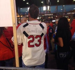 "A St. Louis Cardinals fan handwrote ""I am Darren Wilson"" on a label on the back of his jersey during a clash Oct. 6, 2014, with protesters demanding justice in the case of unarmed Ferguson, Mo., teen Michael Brown, who was fatally shot by Ferguson Police Officer Wilson in August.YouTube screenshot"