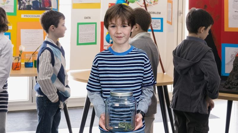 Kid with frog in a jar.