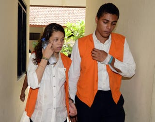 Heather Mack and Tommy Schaefer walk to a courtroom for a trial hearing in Denpasar, on Indonesia's resort island of Bali, March 11, 2015.SONNY TUMBELAKA/AFP/Getty Images