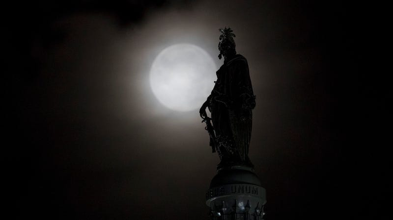 The moon behind the Statue of Freedom in Washington, DC.