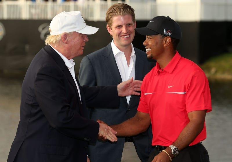 In this March 2013 photo, Donald Trump greets Tiger Woods after the final round of the World Golf Championships-Cadillac Championship as Eric Trump looks on at the Trump Doral Golf Resort & Spa in Doral, Fla.