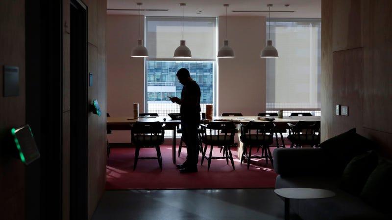 Un empleado revisa su teléfono en una imagen de archivo de las oficinas de Facebook en Cambridge, Massachusetts