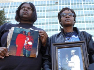 Members of the group Silence Is Violence hold photos of relatives killed in New Orleans. (Associated Press)