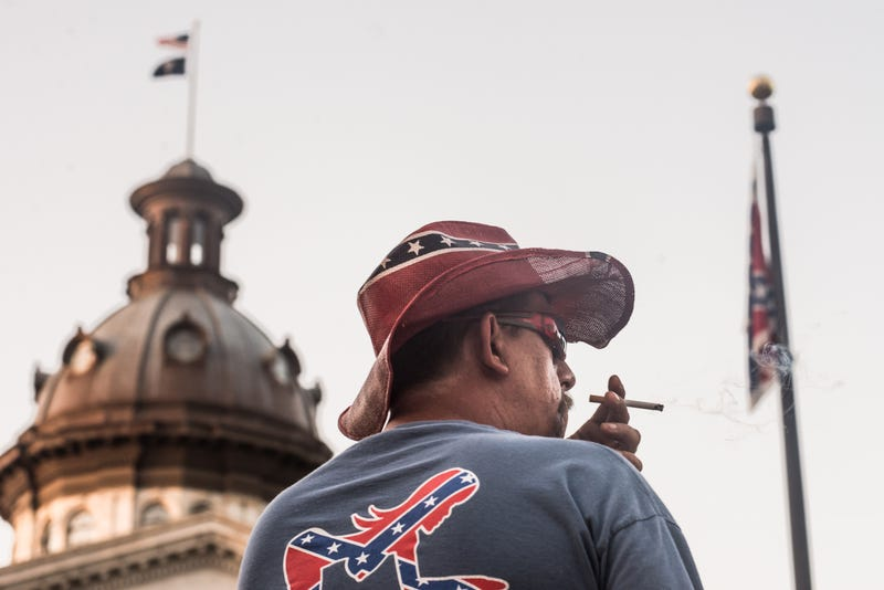 A man watches the sun rise on the Confederate battle flag at the South Carolina Statehouse on July 10, 2015, in Columbia.