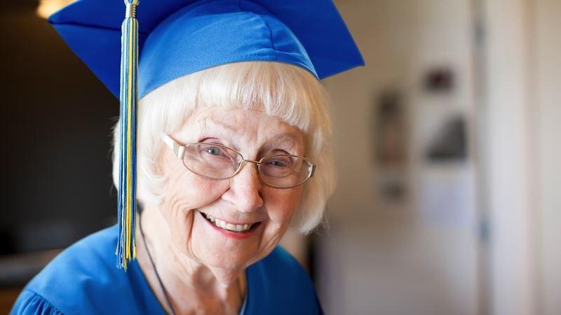 An elderly woman in a graduation cap.