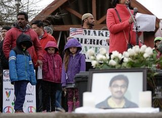 People gather near a photograph of Srinivas Kuchibhotla, the 32-year-old Indian engineer killed at a bar in Olathe, Kan., during a peace vigil in Bellevue, Wash., on March 5, 2017. (Jason Redmond/AFP/Getty Images)