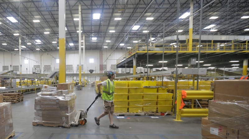 An employee pulls a cart with packages at the Amazon Fulfillment center in Robbinsville Township, N.J., Tuesday, Aug. 1, 2017.