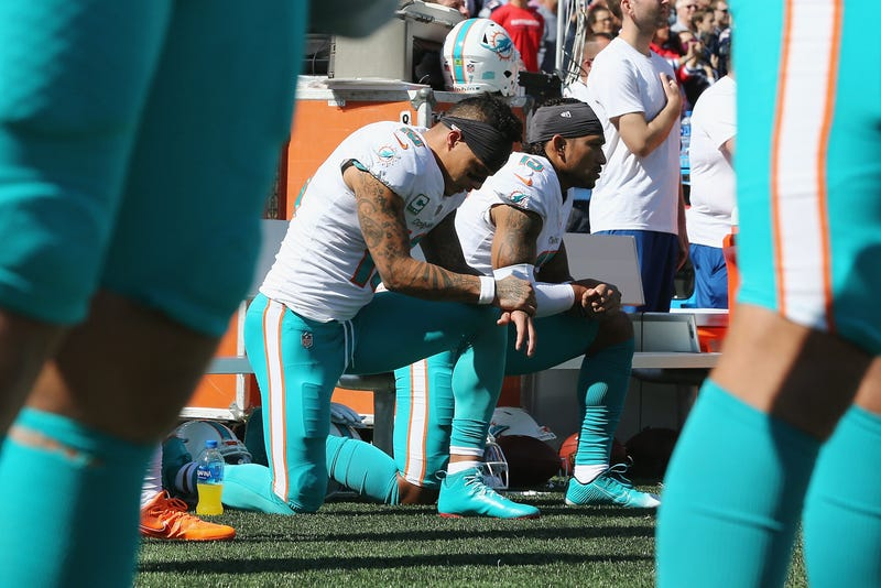 Kenny Stills #10 and Albert Wilson #15 of the Miami Dolphins kneel during the national anthem prior to their game against the New England Patriots at Gillette Stadium on September 30, 2018 in Foxborough, Massachusetts.