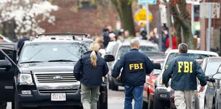 FBI agents comb the streets of Cambridge, Mass., where the writer lives. (Jared Wickerham/Getty Images)