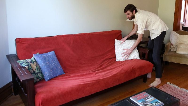 man getting futon all dolled up for craigslist photo shoot  rh   local theonion