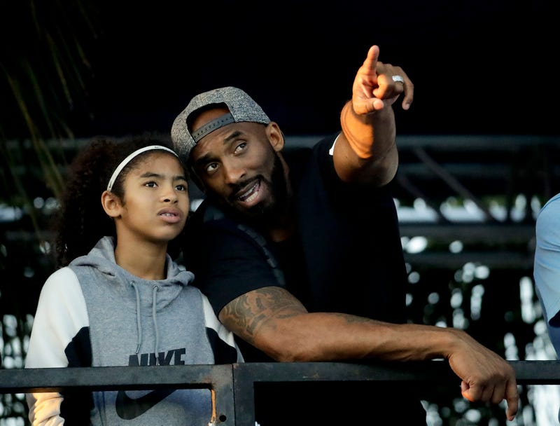 In this file photo legendary Los Angeles Laker Kobe Bryant and his daughter Gianna watch the  U.S. national championships swimming meet Thursday, July 26, 2018, in  Irvine, Calif.