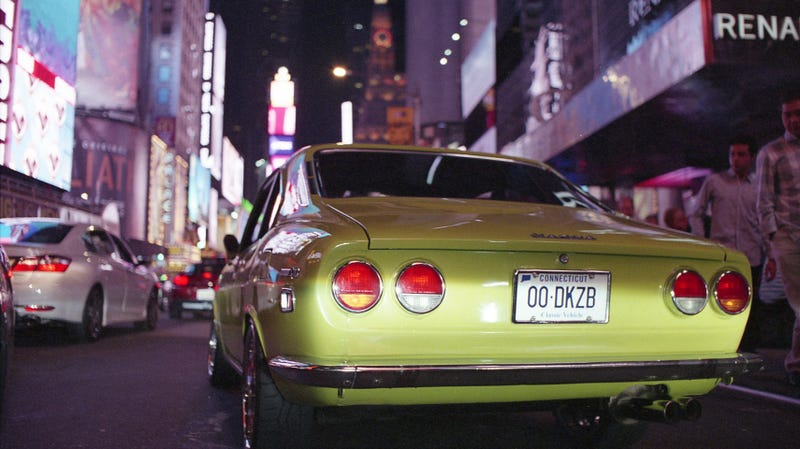 A Mazda RX-2 waits in Time Square traffic as part of the 7s Day run in 2018.