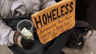 A person in economic difficulty holds a homemade sign asking for money along a New York City street on Dec. 4, 2013.  Spencer Platt/Getty Images