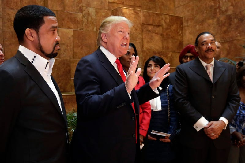 Pastor Darrell Scott (left) listens as then-Republican presidential candidate Donald Trump speaks in Trump Tower  in New York City on April 18, 2016.  (Richard Drew, File/AP Images)