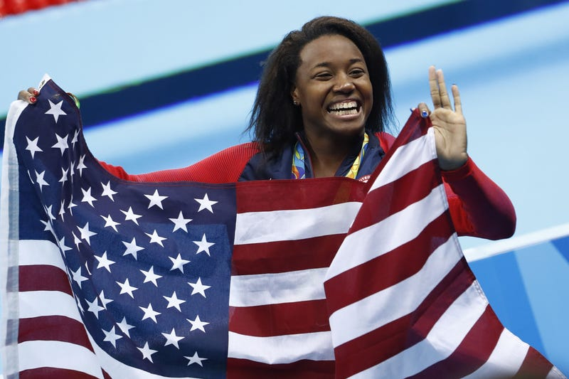 Gold medalist Simone Manuel waves her national flag during the medal ceremony of the Women's 100-meter Freestyle Final at the Rio 2016 Olympics in Rio de Janeiro on Aug. 11, 2016. ODD ANDERSEN/AFP/Getty Images