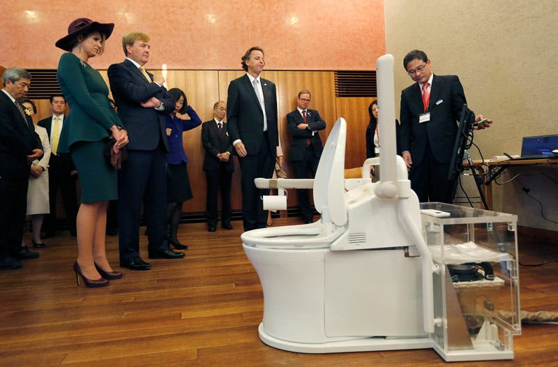 The king and queen of the Netherlands observe a Japanese toilet. Photo: AP