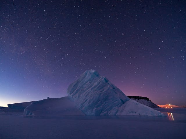 An Iceberg Rises Above The Frozen Water Of Greenland's North Star Bay