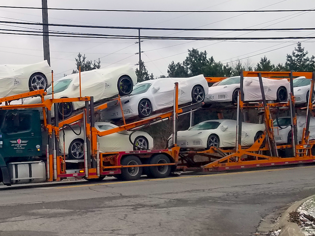 A truck loaded with ten mid-engine Corvettes sits at a stoplight just outside of General Motors' Mil