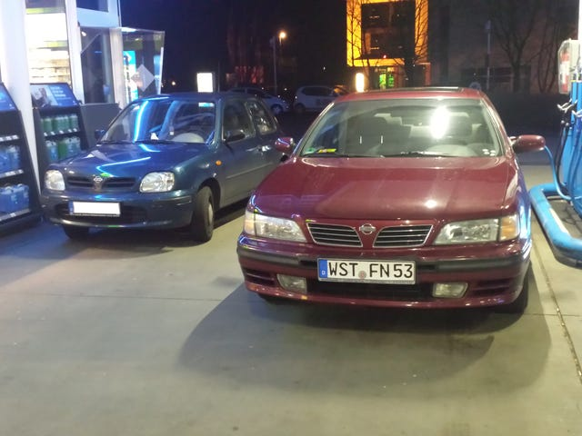 Two 90s BMWs at a petrol station.