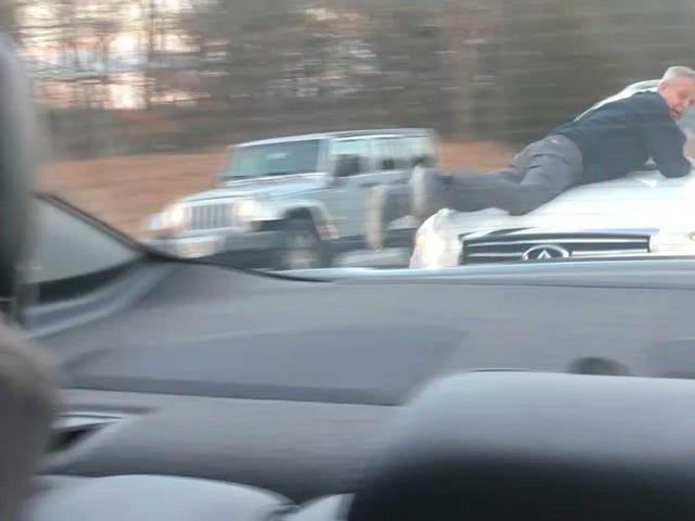 Ο άνθρωπος κολλάει στην κουκούλα του εικαζόμενου αυτοκινήτου του Assaulter στο περιστατικό μαζικής παγίδευσης οδικής οργής, τελειώνει με τον οδηγό που κρατιέται στο Gunpoint