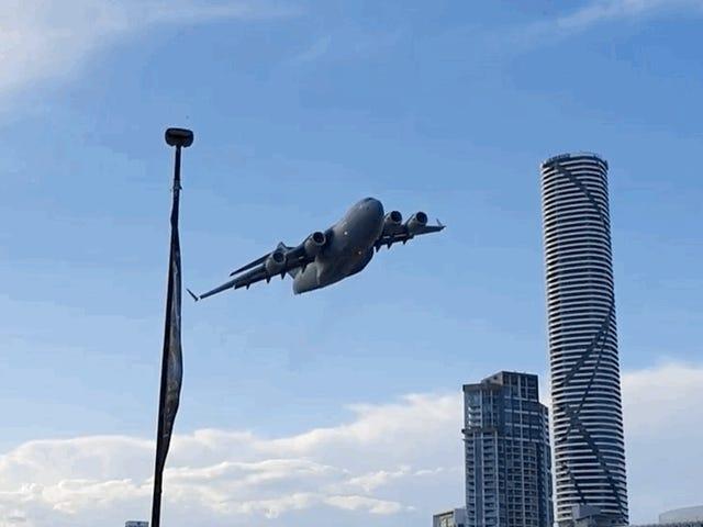 Beobachten Sie, wie ein Frachtjet der australischen Luftwaffe ungezwungen zwischen Brisbanes Wolkenkratzern fliegt