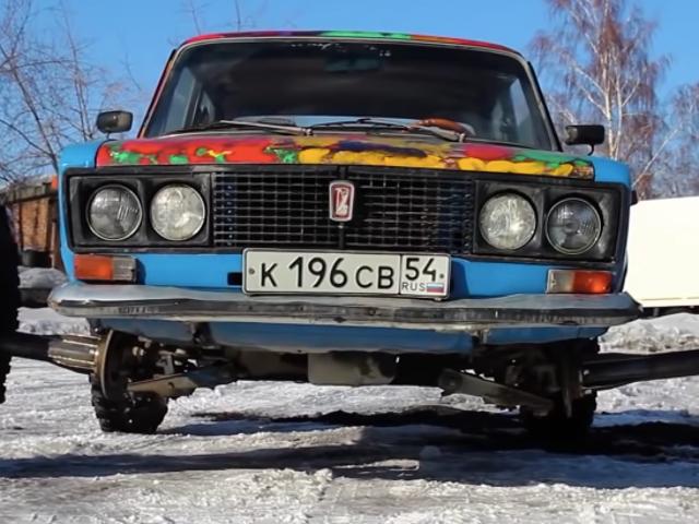 Чоловік кладе 38-дюймові позашляхові шини на російський седан, використовуючи величезні розпірки для коліс, розрізаючи пончики