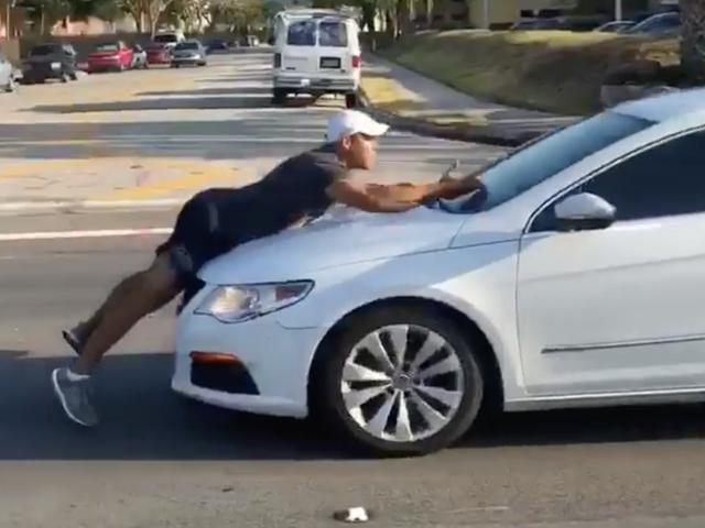 Ο άνθρωπος εκτελεί το επιχείρημα οδικής οργής στην κουκούλα ενός άλλου αυτοκινήτου