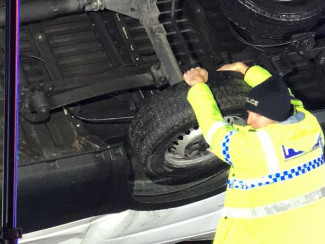 El policía se aferra al camión que cuelga para evitar que se escape de un puente