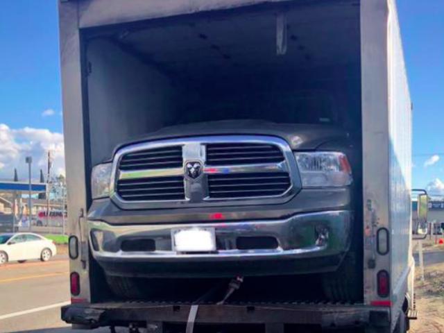 La polizia tira su un camion della scatola con un pickup di ram spremuto quasi impossibile all'interno
